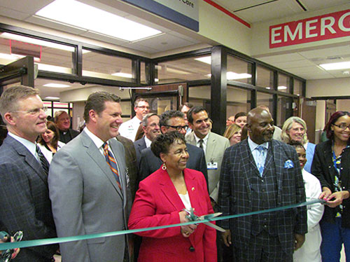 """Joined by staff members and administrators as they prepare to cut ribbon during """"ECMC Center for Orthopaedic Care"""" grand opening event held Thursday, April 7, 2016 (shown front row left to right) are: ECMC Orthopaedics chief of service Dr. Philip Stegemann; ECMC Corp. president & CEO Thomas Quatroche, PhD; ECMC Corp. board chair Sharon Hanson (with scissors); ECMC Corp. board vice chair Michael Seaman (second row); and ECMC Corp. board treasurer Bishop Michael Badger."""