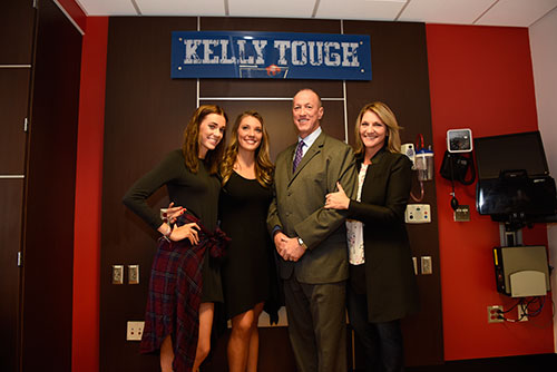 """(l. to r.) Camryn, Erin, Jim and Jill Kelly pose below sign in """"Kelly Tough Room"""" at ECMC."""