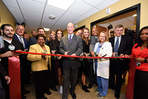"""Jim and Jill Kelly, daughters Camryn and Erin (center) and other family members are surrounded by physicians, ECMCC board members including board chair Sharon Hanson (front row, third from left) and ECMCC Pres. & CEO Tom Quatroche (second row, behind Hanson) and other administrators as they cut the ribbon during the """"Kelly Tough Room"""" dedication at ECMC on October 18, 2016."""