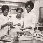 Mrs. Ethel Hicks, kitchen supervisor; Mrs. Ada Hinkle, cook; and Mrs. Helen Evan, food service helper, serve corn bread, ham hocks and cabbage as part of a special 'Soul Food Dinner' at Meyer Memorial Hospital, ca. 1960s.