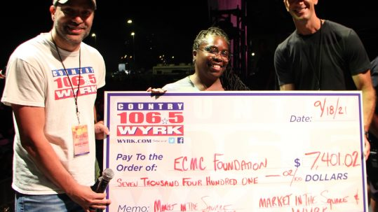Michelle Seay, RN, FNP, DNP-Candidate, Clinical Patient Care Liaison, ECMC (center) accepts check to ECMC Foundation from Dave Fields (left) and Clay Moden (right) of WYRK in the amount of $7,401.02 for funds raised from the Famous Polish Cheesecake Donut challenge (7/30/21-9/17/21) in support of ECMC's courageous frontline caregivers.